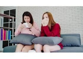 亚洲女同性恋夫妇在家中起居室看电视时哭泣_4015332