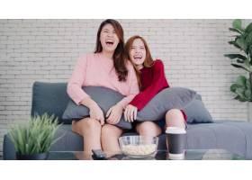 亚洲女同性恋夫妇在家客厅看电视笑吃爆米花_4014701