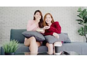 亚洲女同性恋夫妇在家客厅看电视笑吃爆米花_4015329