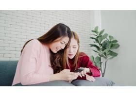 亚洲女性在家中用智能手机查看社交媒体一_4015337