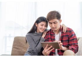 亚洲年轻女子和帅哥坐在沙发上使用设备_5392721