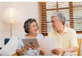 亚洲老年夫妇在家中用平板电脑在客厅看电视_4396364