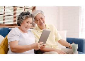 亚洲老年夫妇在家中的客厅里使用平板电脑和_4396331