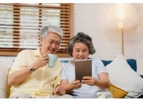 亚洲老年夫妇在家中的客厅里使用平板电脑和_4396370