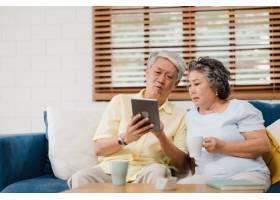 亚洲老年夫妇在家中的客厅里使用平板电脑和_4396371