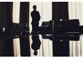 一个孤独的人站在房间的窗户前_1275208