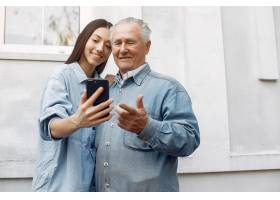 一位年轻的妇女在教她的祖父如何使用电话_7121839
