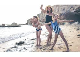 一位年轻的母亲和两个小女儿在海边嬉戏跳_13413382