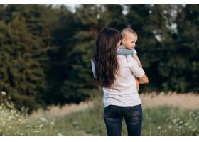 一位年轻的黑发母亲带着她的小女儿走过田野_3337380