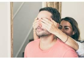 一位快乐的年轻女子用手捂住他的男朋友的眼_13145841