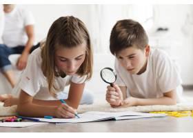 一个男孩在他姐姐画书时透过放大镜看_5116571