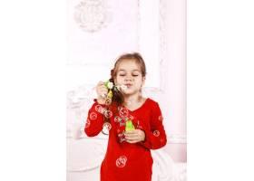 一个穿着红色睡衣的小女孩在室内玩泡泡_7250338