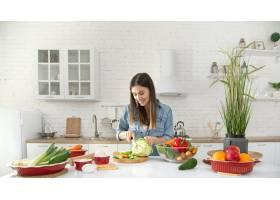 一位年轻漂亮的女士正在厨房准备各种蔬菜沙_9513372
