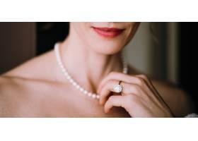一名女子摸着脖子上娇嫩的珍珠项链_3983064