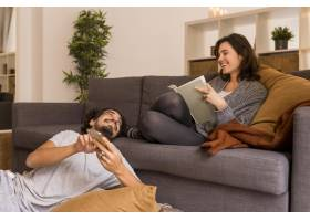 一名年轻女子在起居室里看书旁边坐着她的_12067193
