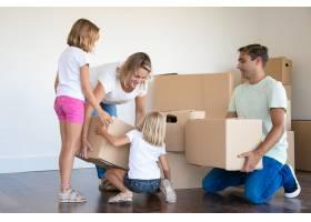 母亲父亲和两个女儿在客厅里有纸箱_11072755