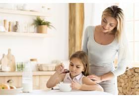 母亲看着女儿吃早餐_10604634