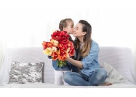 母亲节手持鲜花的小女儿祝贺她的母亲_9045638