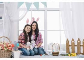 母女俩坐在一起抱着毛绒兔子庆祝复活节_3978649