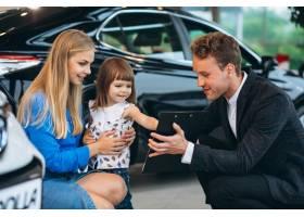 母女在汽车展厅与销售人员交谈_5157732
