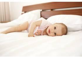 漂亮可爱的新生儿肖像舌头躺在家里的床上_9028470