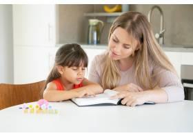 漂亮妈妈带着女儿在厨房看书_9988602