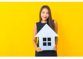 漂亮的年轻亚洲女商人肖像黄色背景上有家_13001654