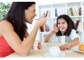漂亮的母亲和她的女儿在家吃酸奶_1139752