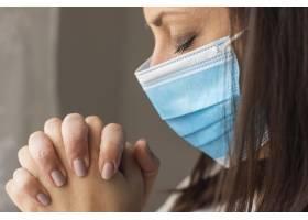 特写成年妇女戴着外科口罩祈祷_8510855
