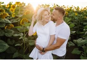 男人和孕妇温柔地拥抱在田野里身边围着高_12970882