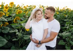 男人和孕妇温柔地拥抱在田野里身边围着高_12970886