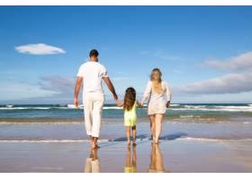 男人女人和孩子穿着苍白的夏装走在潮湿_11072715
