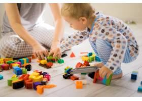 男孩和妈妈穿着五颜六色的建筑工具包玩耍_1537332