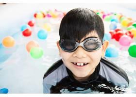男孩在小游泳池玩具里玩五颜六色的球_5192674