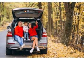 秋天公园的一家人带着一个小儿子坐在车里_3395987