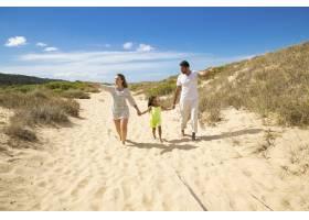 年轻的家庭夫妇和穿着夏装的小孩子沿着白色_11081396