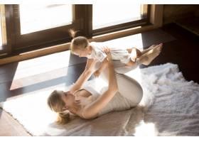 年轻的微笑瑜伽妈妈和小女儿在家里锻炼_3938876
