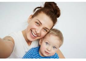 年轻的母亲和她一岁的小儿子穿着睡衣摆姿势_10271288