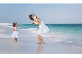 年轻的母亲和她的小女儿在海边的海滩上_5175761