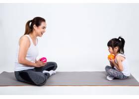 年轻的母亲在白色背景上与可爱的女儿玩耍_5153067