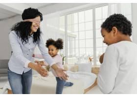 微笑的母亲在家里和她的孩子们玩耍_13108844