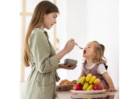 微笑的母亲在给女儿喂奶_8445687