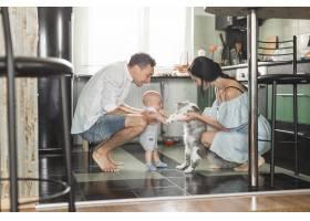 微笑的父母在厨房里和猫和他们的孩子玩耍_3279866