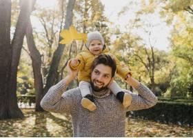 微笑的爸爸带着他的孩子在外面的大自然里_11904667