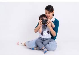 年轻的母亲用白色相机教她的儿子_5395715