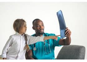年轻的非洲男儿科医生向孩子解释x光_7401685