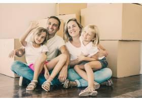 微笑的一家人孩子们坐在纸箱附近的地板上_13145898