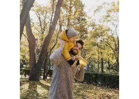 微笑的爸爸带着他的孩子在户外的大自然中_11904666