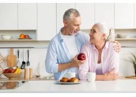 微笑着的成熟恩爱夫妇一家人站在厨房里_7340381