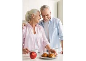 微笑着的成熟恩爱夫妇一家人站在厨房里_7340391